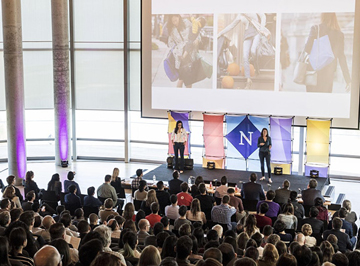 A crowd watches a pitch competition in White Auditorium in the Kellogg Global Hub
