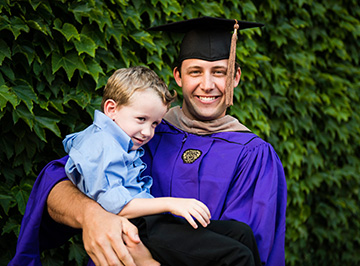 A Kellogg graduate poses with his young son against a lush background.