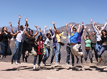 Students jump and pose mid air in a mountainous region.
