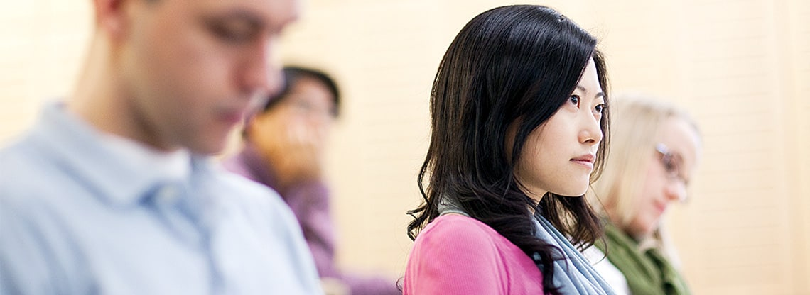 A young woman in a pink shirt participates in the Kellogg two-year MBA program.