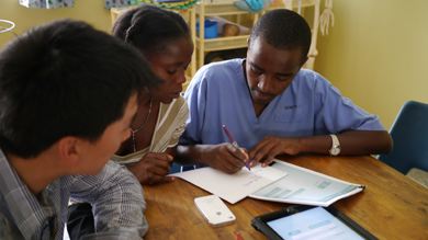 Eric Chang '13 (left) demonstrates the Northwestern Global Health Foundation's tablet prototype to two nurses in a clinic in Mbarara, Uganda. Chang was one of 34 Northwestern students in the inaugural Innovate for Impact course this year.