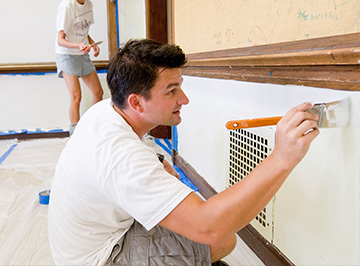 A young man volunteers by painting a classroom.